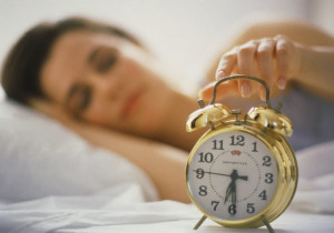 Woman Lying in Bed and Turning Off Alarm Clock
