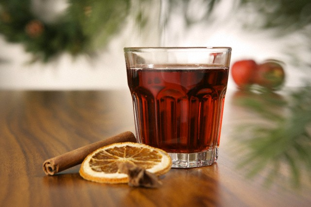 Glass of mulled wine with cinnamon stick and slice of orange