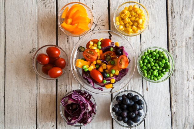 Mixed salad and glass bowls with different raw vegetables rainbow-coloured arranged on white wood