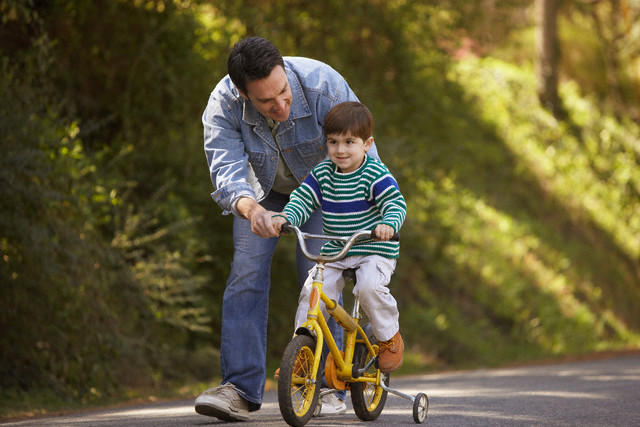Father Teaching Boy Riding a Bicycle