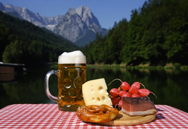 Garmisch-Partenkirchen, Germany --- Germany, Upper Bavaria, Bavarian snacks on table, mountain with lake in background --- Image by © Tom Chance/Westend61/Corbis