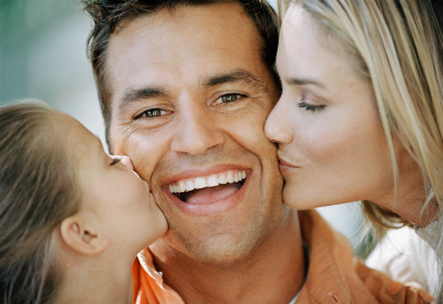 Woman and Daughter Kissing Man on Cheeks --- Image by © Laureen March/CORBIS